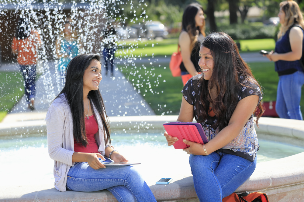 students sitting by fountain